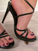 Xenia crushes a small cigar under her high heels
